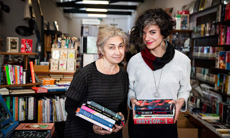 ladies holding a stack of books