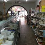 Inside of back end of supermarket where the deli is and bagged nuts