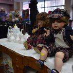 2 dolls sitting on a cabinet