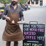 Man in apron holding breakfast next to chalkboard