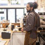 Barista in apron at espresso machine