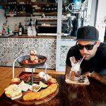 Man drinking milkshake in cafe next to breakfast tower