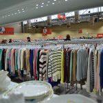 Racks of clothing and shelf of crockery