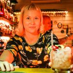Waitress serving cocktail over bar