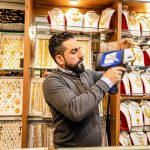Man evaluating gold jewellery item in jewellery store