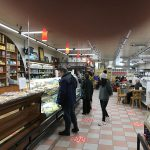 Shoppers in a grocery deli and cafe