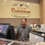 Man behind counter at Pakistani cuisine restaurant