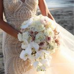 Bride holding floral bouquet with lacy dress