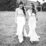 2 ladies in bridal formal gowns holding hands