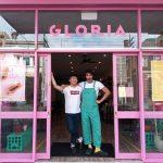 2 men in doorway of pink cafe