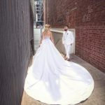 Bride with large train posing in laneway with groom