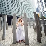 Bride in pants suit with groom posing in the city
