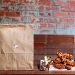 Chicken wings and brown paper takeaway bag