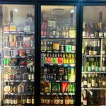 Bottles of wine, mixers and ciders in a fridge