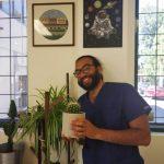 Man in scrubs holding cactus