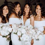 Four ladies posing in white formal dresses with bouquets