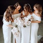 Ladies posing in white formal dresses with bride