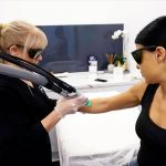 Woman performing laser treatment on another woman