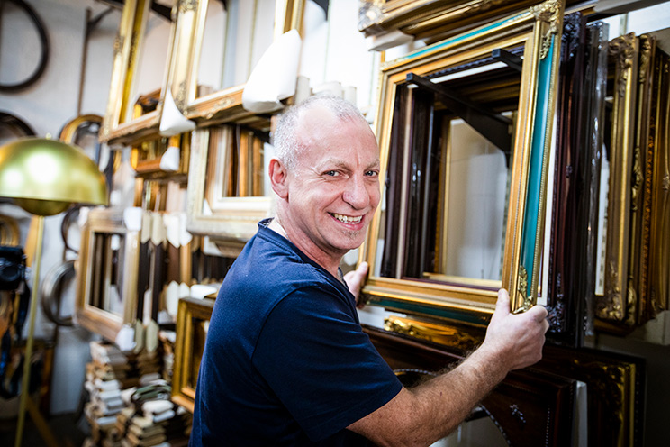 Smiling man holding picture frames