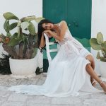 Lady in white sheer dress leaning on chair